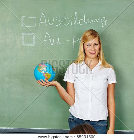 Woman with globe in front of chalkboard with German words for Apprenticeship and Au-Pair written on it