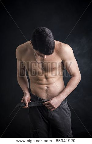 Handsome, Fit Shirtless Young Man Undoing Pants' Belt