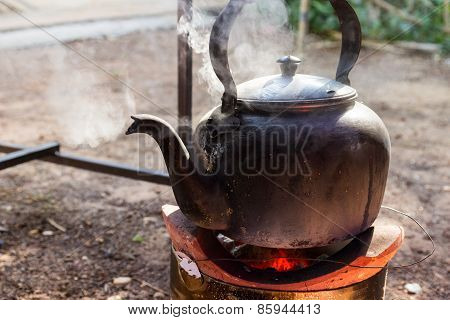 old kettle for boiling water on charcoal stove poster