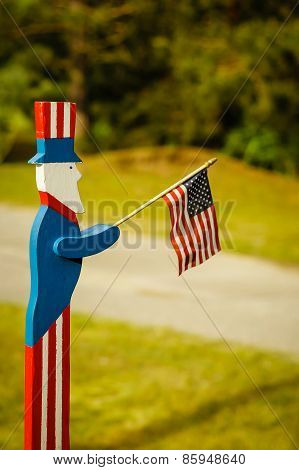 Wooden Uncle Sam waving an American flag. poster
