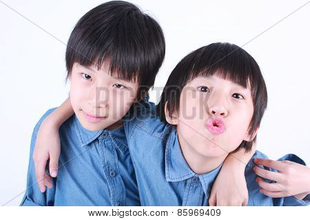 Portrait of two hugging boys, twins with white background.