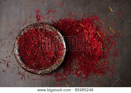 saffron spice threads and powder  in vintage iron dish  old metal background, closeup poster