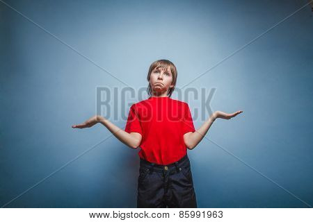 Boy, teenager, twelve years in the red T-shirt, threw up his han