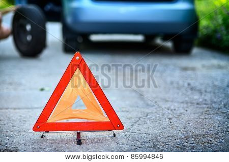 Emergency stop sign in backround with broken down car