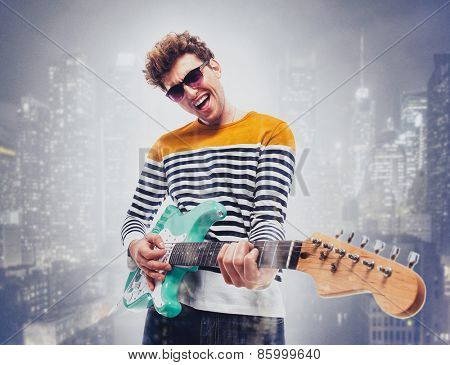 Double exposure of a city and happy man playing guitar