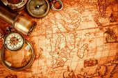 Vintage magnifying glass, compass, telescope and a pocket watch lying on an old map in 1565. poster