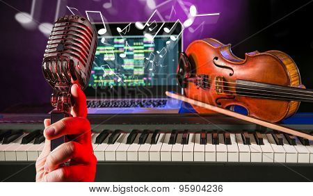 Man with microphone, piano keyboards, old violin and notebook in audio studio.