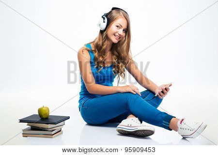 Happy young woman listening music in headphones on smartphone isolated on a white background. Looking at camera