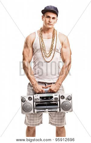 Vertical shot of a young muscular man in hip hop clothes holding a ghetto blaster and looking at the camera isolated on white background