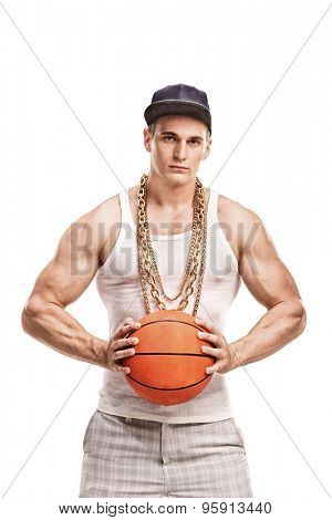 Vertical shot of a muscular young man in hip hop outfit holding a basketball and looking at the camera isolated on white background
