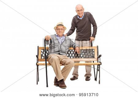 Full length portrait of a two senior old friends posing together seated on a wooden bench isolated on white background