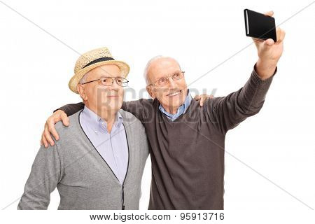 Studio shot of two senior men taking a selfie with cell phone and smiling isolated on white background