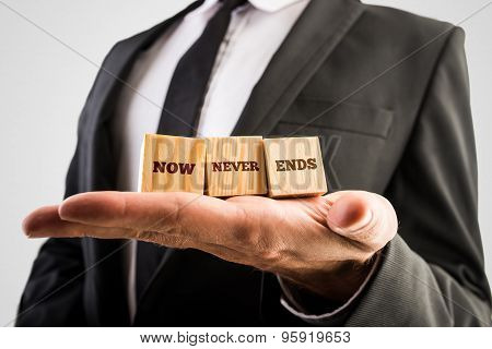 Closeup Of Spiritual Teacher Or Mentor Holding Up  Three Wooden Cubes With A Now Never Ends Sign