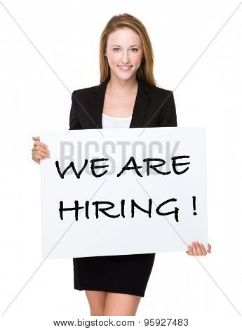 Businesswoman show a white poster with phrase of we are hiring