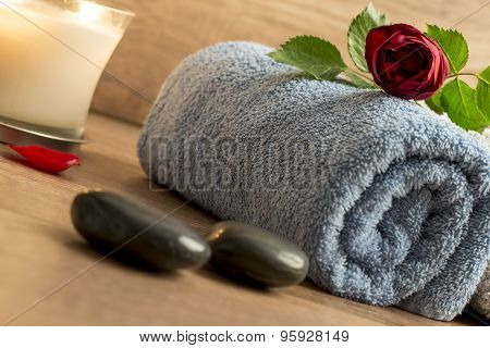 Luxurious Wellness Arrangement With A Rolled Blue Towel, Red Rose, Burning Candle, And Two Black Mas