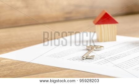 Silver house key lying on a contract of house sale lease insurance or mortgage in a real estate concept viewed low angle with focus to the tip. poster