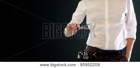 beauty and hair salon, hairstyle and people concept - close up of male stylist with scissors over blank black background