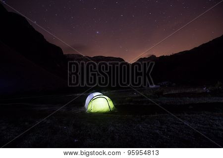 Tent Standing On A Mountain Pasture Under Starry Sky