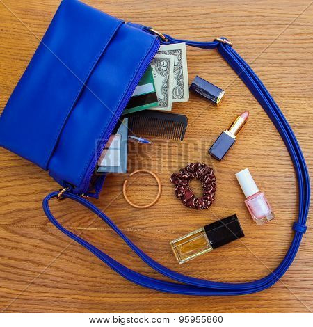 Things from open lady handbag. women's purse on wood background.