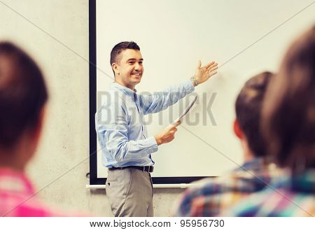 education, high school, technology and people concept - smiling teacher with notepad, laptop computer standing in front of students and showing something on white board in classroom