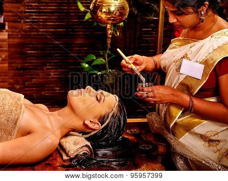 Woman with closed eyes having facial mask at ayurveda spa.