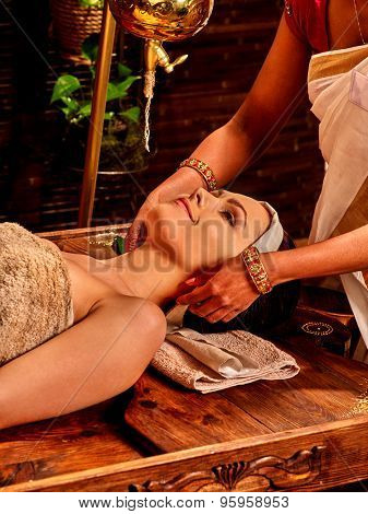 Woman having facial ears ayurveda spa treatment.