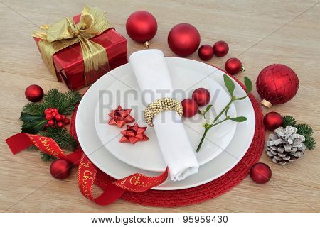 Christmas dinner place setting with plates, cutlery, napkin, holly and mistletoe, red baubles and gift box over light oak background.