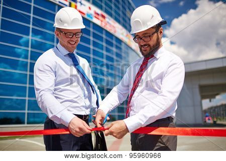 Happy architect cutting red ribbon at official opening of new construction
