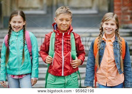 Group of cute schoolmates with backpacks looking at camera