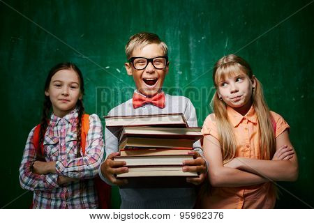Ecstatic pupil with books standing between two schoolmates