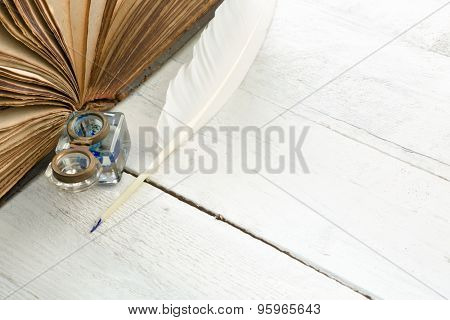 Feather quill, blue ink pot and medieval book on a rustic white painted table