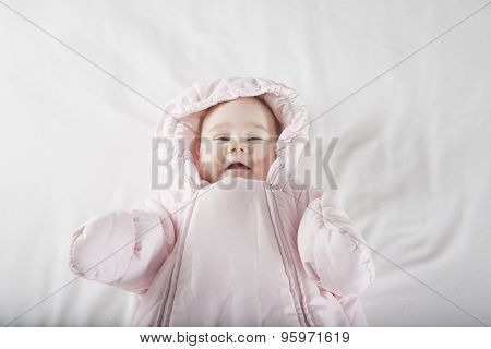 Smiling Baby Face Wrapped In Pink Snowsuit