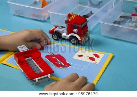 Young asian boy building lego with instruction manual