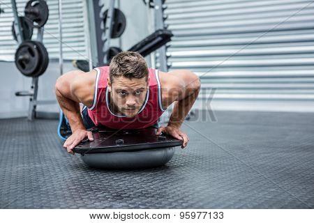 Portrait of muscular man using bosu ball in crossfit gym