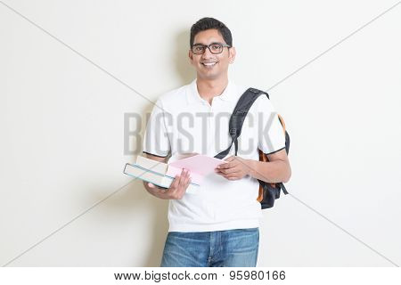 Portrait of adult Indian college student with bag and books. Asian man standing on plain background with shadow and copy space. Handsome mixed race male model.
