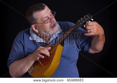 Portrait of a senior tuner with mandolin