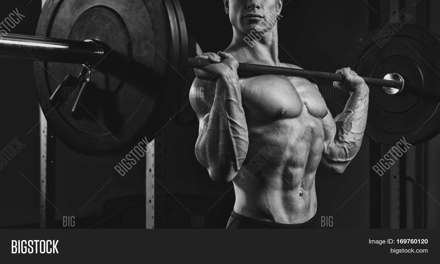 Black and white close up photo of man doing a lifting workout on dark background at
