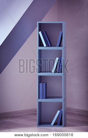 Blue wooden shelving with books on gray wall background
