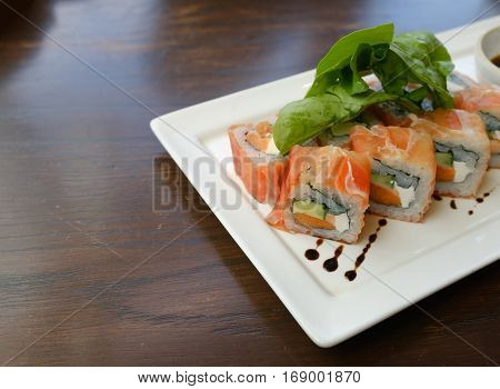 fusion salmon sushi rolls with sauce on white plate; healthy and fusion japanese food style concept