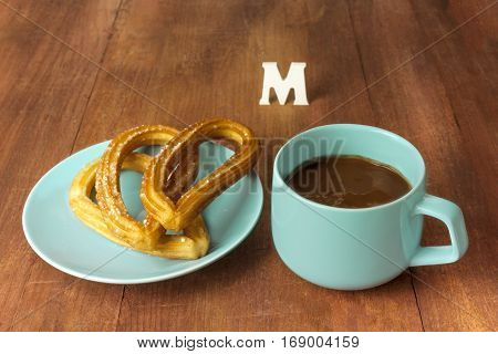 Churros, traditional Spanish, especially Madrid, dessert, often for Sunday breakfast, in form of horseshoe, with cup of chocolate on wooden board texture, retro style, with copyspace and letter M