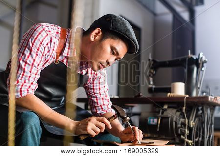 Asian shoe or belt maker in his leather workshop with sawing machine in background