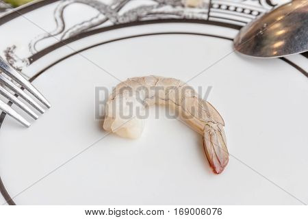 A raw fresh shrimp served on luxury ceramic plate (blurred focus background) with spoon and fork in Thai seafood restaurant.