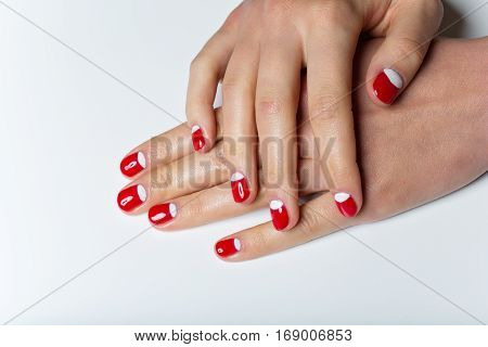 Close-up shot of young femle hands with red and white nail manicure. Copy space.