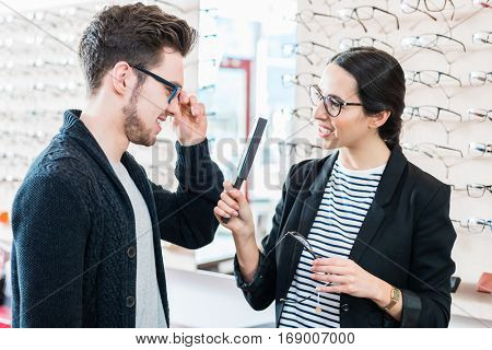 Woman and man buying glasses in optician shop