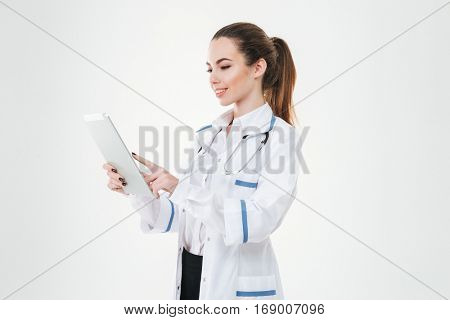 Happy beautiful young woman doctor using tablet computer over white background