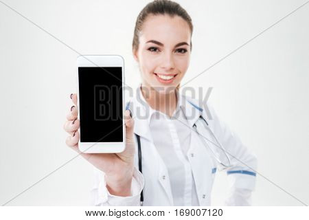 Cheerful cute young woman doctor showing blank screen mobile phone over white background