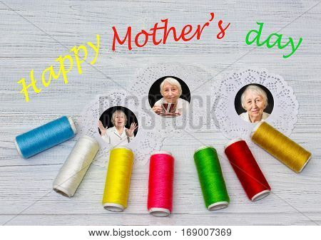Mothers day composition. The photos, wooden background with bobbins with colorful threads . Happy mother's day concept