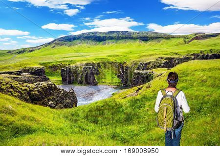 Green Tundra in summer. The elderly woman -  tourist with big backpack admiring the magnificent scenery. The concept of active northern tourism. The striking canyon in Iceland