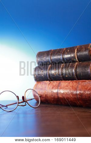 Stack of old book near spectacles on blue background with free space