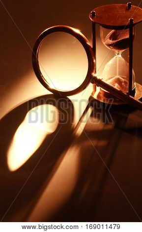 Vintage hourglass near magnifying glass on dark background with long shadow